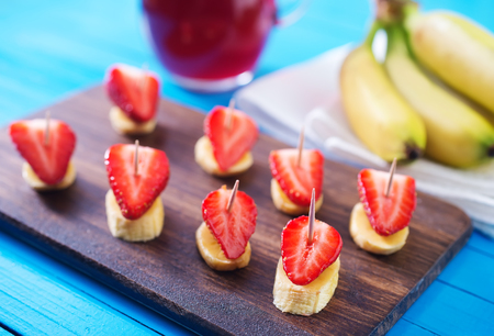 canape with strawberry and banana on wooden board