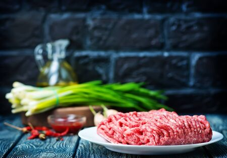 raw minced meat on plate and on a table