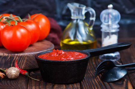 tomato sauce and fresh tomato on a table Stock Photo