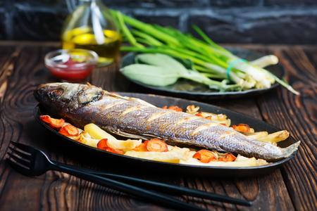 gebakken vis met plantaardige op een tafel