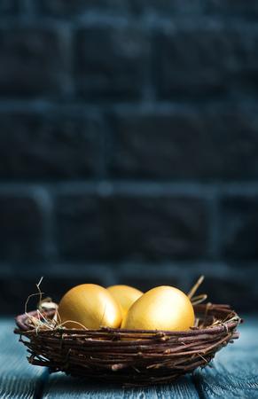Huevos de oro, huevos de Pascua en una mesa Foto de archivo - 72404839
