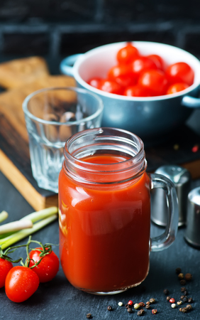 tomato juice in glass bank and on a table