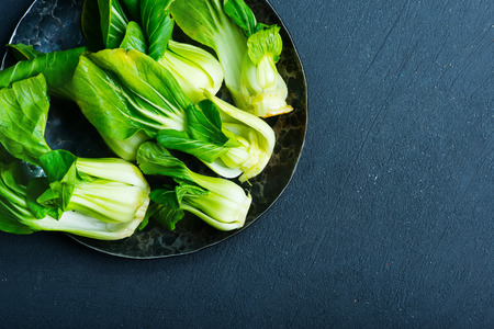 fresh pak choi on plate and on a table