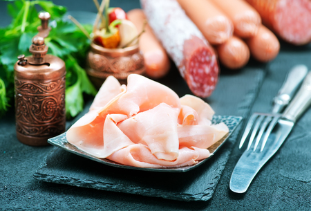 air dried salami: mix sausages on board and on a table Stock Photo