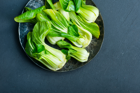 syn: fresh pak choi on plate and on a table