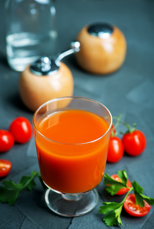 tomato juice in glass and vodka on a table