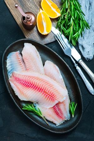 tilapiini: raw fish with spice on a table