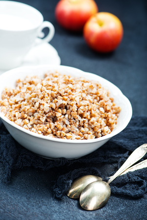 boiled buckwheat in bowl and on a table Stock Photo - 77020089