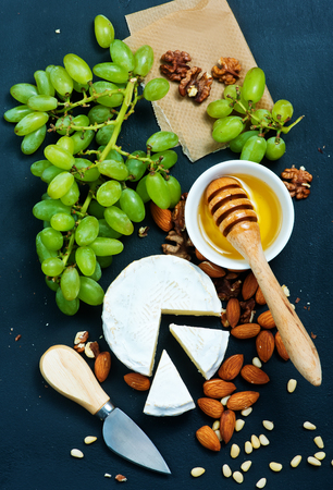 cheeseboard: cheese with honey and nuts on a table