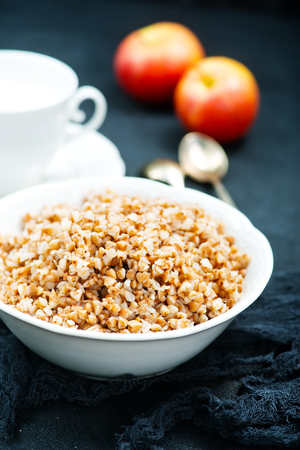 boiled buckwheat in bowl and on a table Stock Photo
