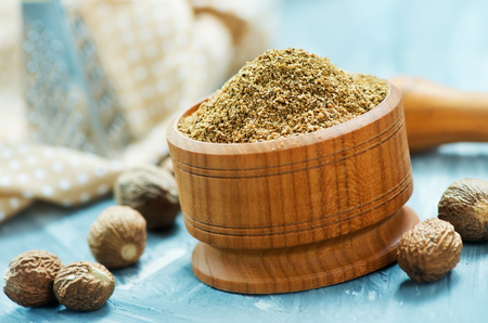 nutmeg and powder in bowl and on a table Stock Photo