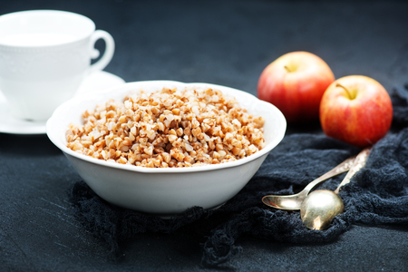 boiled buckwheat in bowl and on a table Stock Photo - 77022206