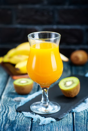 キウイとバナナのガラスのテーブルの上からジュース