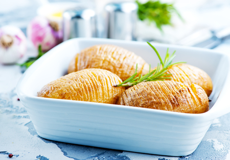 baked potato with rosemary and garlic in bowl Stock Photo