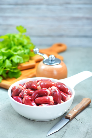 raw chicken hearts in bowl and on a table