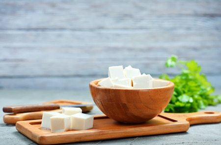 Tofu-Käse in Schüssel und auf einem Tisch Standard-Bild - 79458863