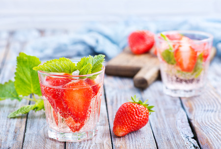 strawberry drink in glass and on a table