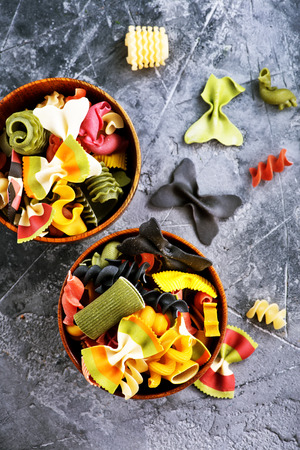 color raw pasta in bowl and on a table Stock Photo