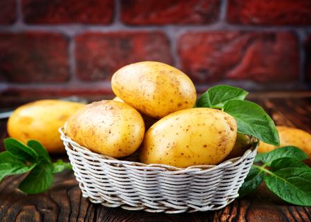 바구니에있는 원시 감자와 테이블