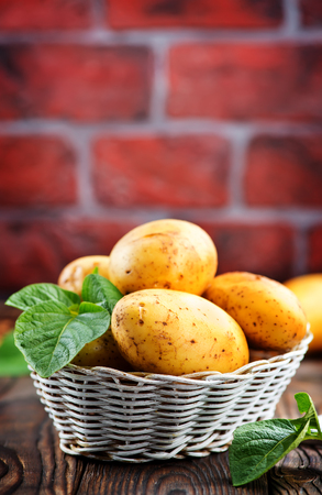 raw potato in basket and on a table Banco de Imagens - 80795675