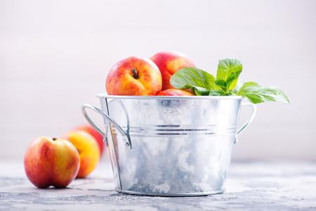 nektarines in metal bowl and on a table Stock fotó