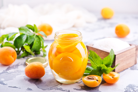 apricots with sirup in glass bank and on a table