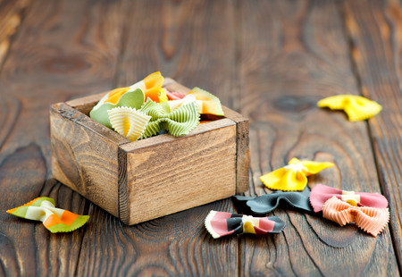 mee: color raw pasta in wooden box and on a table