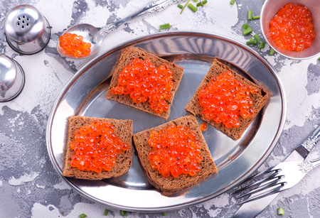 bread with red salmon caviar on metal plate Imagens
