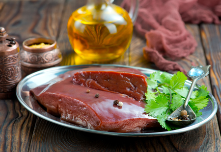 raw liver on plate and on a table