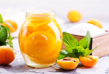 marmelade: apricots with sirup in glass bank and on a table