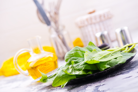 ze: raw spinach on plate and on a table Stock Photo