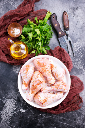 raw chicken legs with spice and salt