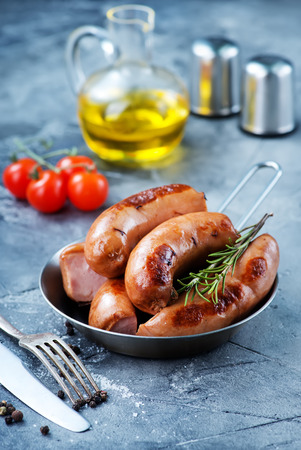 fried sausages in pan and on a table Stockfoto