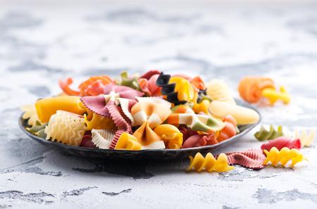 Pasta cruda en un plato y en una mesa Foto de archivo - 81263521