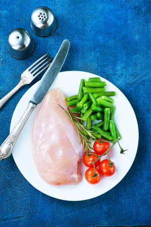 raw chicken fillet and green beans on plate
