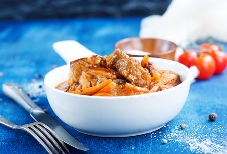 meat stew in white bowl and on a table