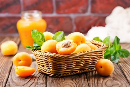 verse abrikozen in mand en op een tafel Stockfoto
