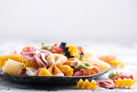 raw pasta on plate and on a table