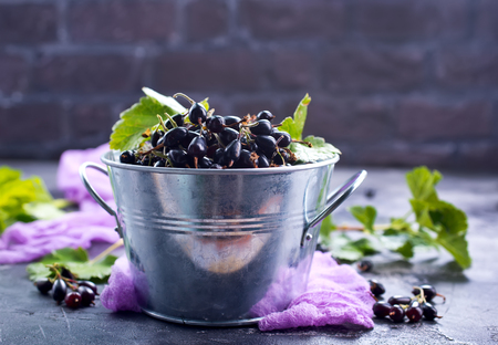 black currant in bowl and on a table Stok Fotoğraf