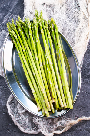 raw asparagus on metal plate and on a table