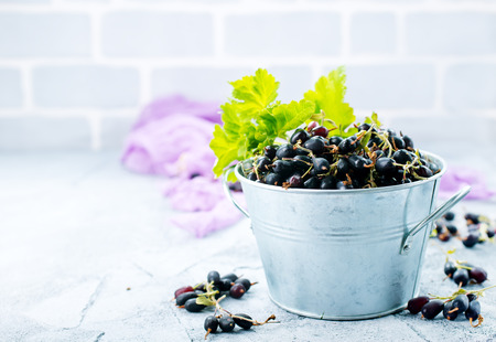 black currant in bowl and on a table Stock Photo
