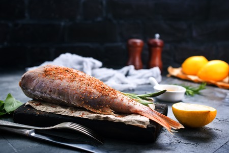 gilt head: raw fish with spice and salt on a table