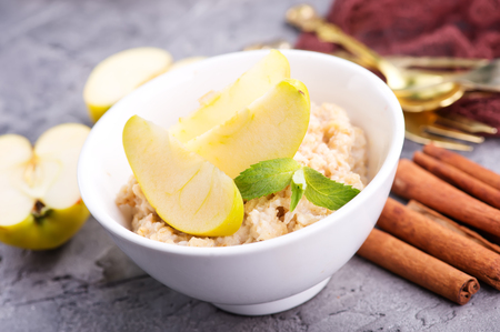 Oatmeal with fresh apples and cinnamon in the bowl Stock Photo