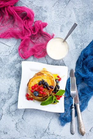 pancakes with berries on plate and on a table Banco de Imagens