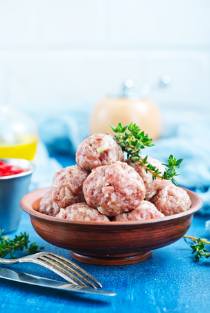raw meatballs with spice and salt on a table