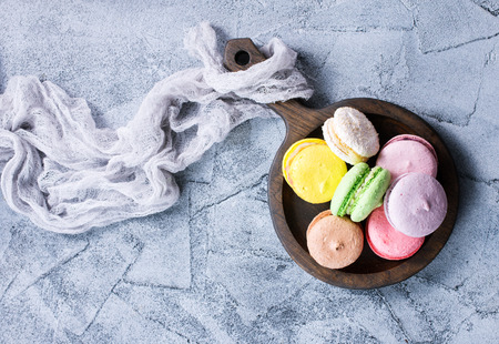 macaroons on wooden plate and on a table