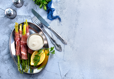 green asparagus with bacon on a table