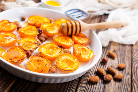 baked apricots with honey and nuts on a table Reklamní fotografie - 82957444