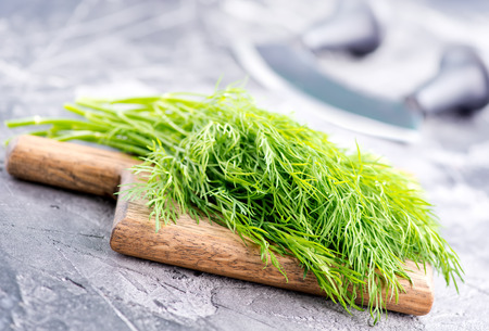 fresh dill on board and on a table Banco de Imagens - 82978261