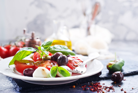 caprese salad on plate and on a table Stock Photo